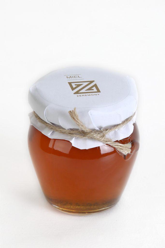 Esta miniatura de miel tiene forma ovoide achatada con base redonda. Está decorado con todo el capricho con un papel en el que se puede ver la elegancia de la marca Zeremony y un lacito.