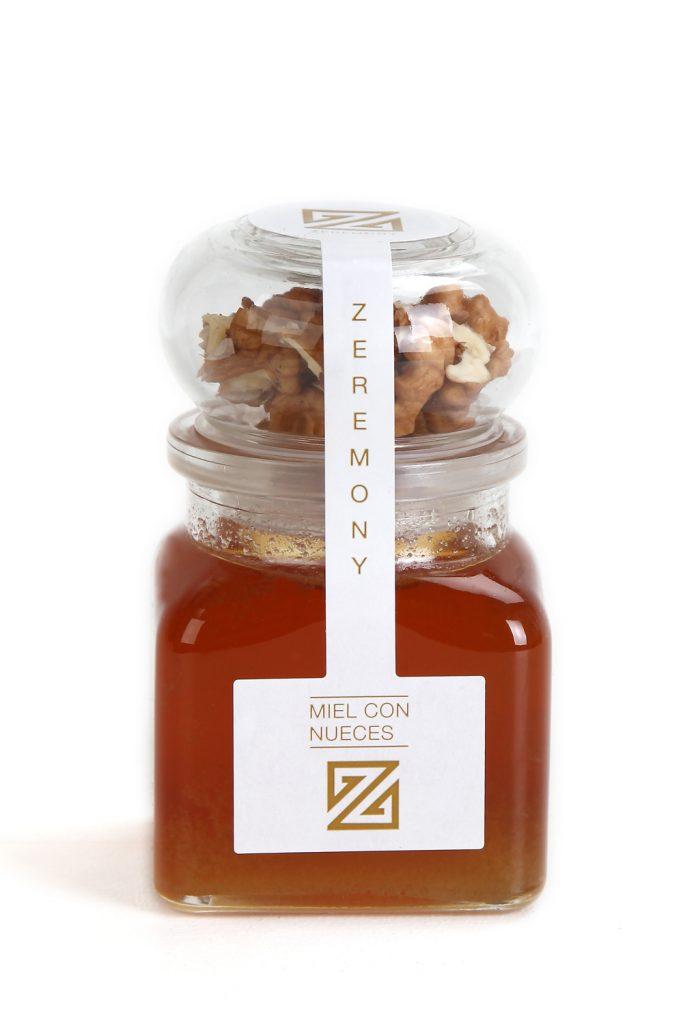 Preciosa miniatura de miel con forma cuadrada y tapón de forma circular repleto de almendras o nueces, quedando a la elección del cliente.
